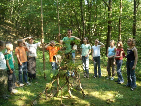 Kinder mit Teamer im Wald im Halbkreis