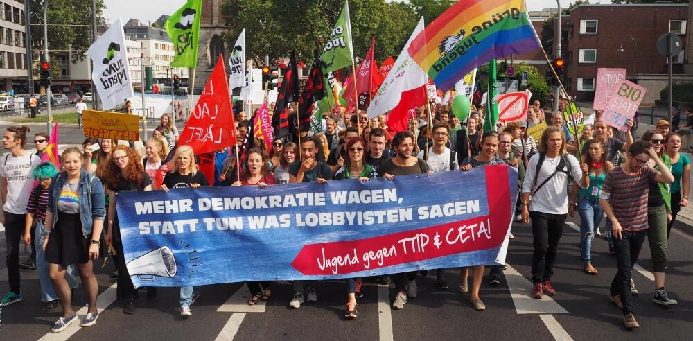 junge Menschen bei einer TTIP Demo mit Banner und Fahnen (Aktivenpool BUNDjugend NRW)